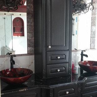 Esempio di una stanza da bagno padronale tradizionale di medie dimensioni con ante con bugna sagomata, ante nere, vasca sottopiano, doccia a filo pavimento, bidè, piastrelle bianche, piastrelle in pietra, pareti rosse, pavimento in marmo, lavabo a bacinella e top in granito