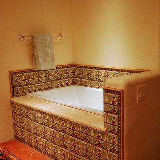 アルバカーキの中サイズのサンタフェスタイルのおしゃれな子供用バスルーム (落し込みパネル扉のキャビネット、緑のキャビネット、ドロップイン型浴槽、マルチカラーのタイル、セラミックタイル、ベージュの壁、テラコッタタイルの床、アンダーカウンター洗面器、大理石の洗面台) の写真