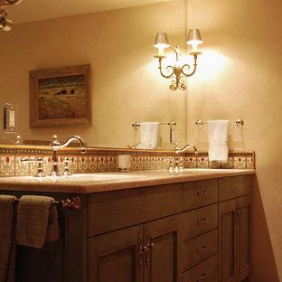 アルバカーキの中サイズのエクレクティックスタイルのおしゃれなマスターバスルーム (インセット扉のキャビネット、青いキャビネット、ドロップイン型浴槽、コーナー設置型シャワー、マルチカラーのタイル、モザイクタイル、ベージュの壁、アンダーカウンター洗面器、珪岩の洗面台) の写真