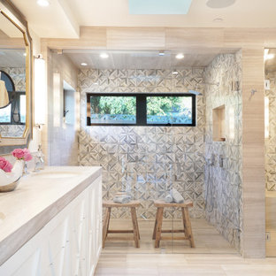 Example of a large french country master gray tile and marble tile limestone floor and gray floor double shower design in Orange County with furniture-like cabinets, gray cabinets, a two-piece toilet, white walls, an undermount sink, limestone countertops, a hinged shower door and gray countertops