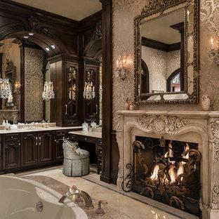 Aménagement d'une salle de bain méditerranéenne avec des portes de placard en bois sombre, une baignoire posée et un placard avec porte à panneau surélevé.