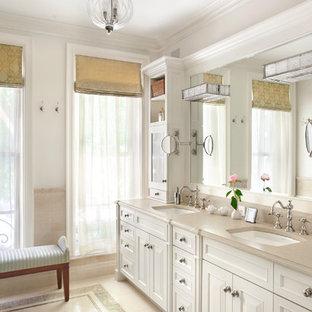 Immagine di una grande stanza da bagno padronale chic con lavabo sottopiano, ante con riquadro incassato, ante bianche, top in pietra calcarea, piastrelle beige, lastra di pietra, pareti beige e pavimento in pietra calcarea