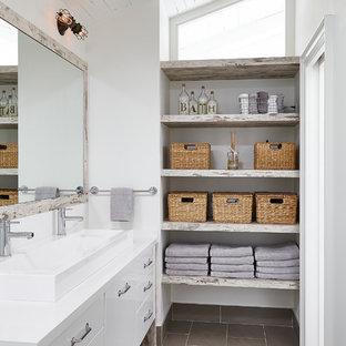 Ejemplo de cuarto de baño con ducha, tradicional renovado, de tamaño medio, con armarios con paneles lisos, sanitario de dos piezas, paredes blancas, suelo de baldosas de porcelana, lavabo de seno grande, puertas de armario blancas, baldosas y/o azulejos beige, encimera de acrílico y encimeras blancas