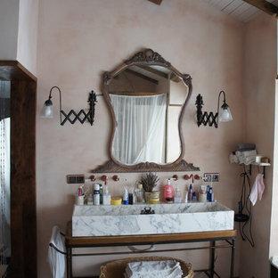 Foto de cuarto de baño bohemio con lavabo de seno grande, paredes beige y suelo de madera oscura