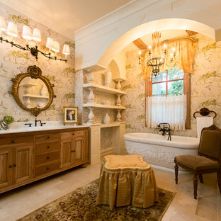 Inspiration for a french country freestanding bathtub remodel in Houston with medium tone wood cabinets, a drop-in sink and raised-panel cabinets