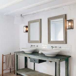 This is an example of a large mediterranean master bathroom in Toulouse with distressed cabinets, subway tile, white walls, terra-cotta floors, a vessel sink, wood benchtops and blue benchtops.