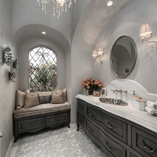 Huge cottage chic master multicolored tile and porcelain tile porcelain floor and multicolored floor bathroom photo in Phoenix with furniture-like cabinets, gray cabinets, a one-piece toilet, white walls, a drop-in sink, marble countertops, a hinged shower door and multicolored countertops