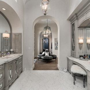 Foto de cuarto de baño mediterráneo con armarios con paneles empotrados, puertas de armario grises, paredes grises, lavabo bajoencimera y suelo blanco