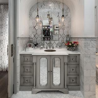 Imagen de cuarto de baño mediterráneo con armarios con paneles empotrados, puertas de armario grises, bañera exenta, ducha empotrada, sanitario de una pieza, baldosas y/o azulejos blancos, baldosas y/o azulejos de porcelana, paredes grises, suelo de mármol, lavabo bajoencimera, encimera de mármol, suelo blanco, ducha abierta y encimeras multicolor