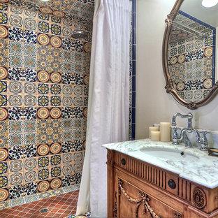 Modelo de cuarto de baño con ducha, mediterráneo, de tamaño medio, con lavabo bajoencimera, puertas de armario de madera oscura, ducha a ras de suelo, baldosas y/o azulejos multicolor, armarios con paneles con relieve, bañera esquinera, sanitario de una pieza, baldosas y/o azulejos en mosaico, paredes grises, suelo de madera clara, encimera de granito, ducha con cortina y encimeras grises