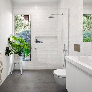 На фото: большая ванная комната в современном стиле с плоскими фасадами, белыми фасадами, открытым душем, инсталляцией, белой плиткой, керамической плиткой, белыми стенами, полом из керамогранита, душевой кабиной, монолитной раковиной, серым полом, открытым душем, желтой столешницей, нишей и подвесной тумбой с