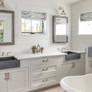 Example of a country beige floor freestanding bathtub design in Boston with recessed-panel cabinets, white cabinets, white walls and white countertops