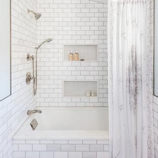 Diseño de cuarto de baño de estilo de casa de campo con bañera encastrada sin remate, combinación de ducha y bañera, baldosas y/o azulejos blancos, baldosas y/o azulejos de cemento y paredes grises