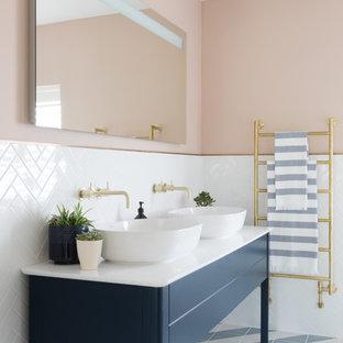 Ejemplo de cuarto de baño principal, costero, con armarios tipo mueble, puertas de armario azules, baldosas y/o azulejos blancos, paredes rosas, lavabo sobreencimera, suelo multicolor y encimeras blancas