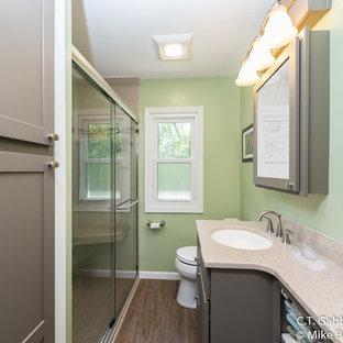 Diseño de cuarto de baño con ducha, tradicional renovado, pequeño, con armarios con paneles empotrados, puertas de armario grises, ducha empotrada, paredes multicolor, suelo laminado, lavabo integrado, encimera de ónix, suelo marrón y ducha con puerta corredera