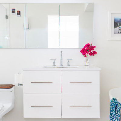 Example of a mid-sized transitional master blue tile and cement tile concrete floor bathroom design in Los Angeles with flat-panel cabinets, white cabinets, a one-piece toilet, white walls, an undermount sink and quartz countertops