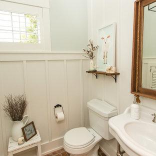 Immagine di una piccola stanza da bagno con doccia country con WC a due pezzi, pareti bianche, pavimento in mattoni e top bianco