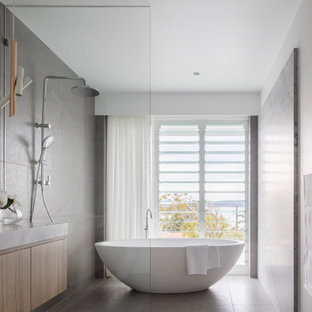 Large contemporary wet room bathroom in Sydney with a freestanding tub, granite benchtops, flat-panel cabinets, light wood cabinets, gray tile, white walls, an undermount sink, grey floor, grey benchtops and a floating vanity.