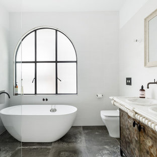 Design ideas for a mid-sized mediterranean master bathroom in Sydney with flat-panel cabinets, distressed cabinets, a freestanding tub, a one-piece toilet, grey walls, an integrated sink, marble benchtops, grey floor, beige benchtops and ceramic floors.