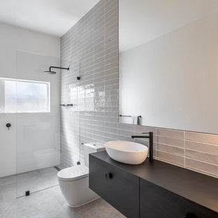 Photo of a contemporary 3/4 bathroom in Adelaide with flat-panel cabinets, black cabinets, a curbless shower, gray tile, white walls, a vessel sink, wood benchtops, grey floor, an open shower and black benchtops.