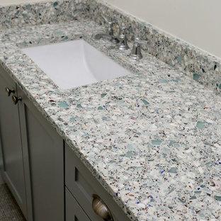 Ejemplo de cuarto de baño actual con lavabo bajoencimera, puertas de armario grises, encimera de vidrio reciclado, bañera empotrada, combinación de ducha y bañera, sanitario de dos piezas y paredes azules