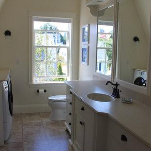 Immagine di una grande stanza da bagno con doccia classica con ante in stile shaker, ante bianche, piastrelle beige, piastrelle in ceramica, pareti beige, pavimento con piastrelle in ceramica, lavabo sottopiano e top in laminato