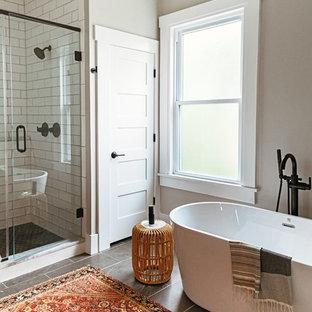 他の地域の小さいコンテンポラリースタイルのおしゃれなマスターバスルーム (シェーカースタイル扉のキャビネット、淡色木目調キャビネット、置き型浴槽、オープン型シャワー、白いタイル、サブウェイタイル、磁器タイルの床、アンダーカウンター洗面器、珪岩の洗面台、黒い床、開き戸のシャワー、白い洗面カウンター) の写真