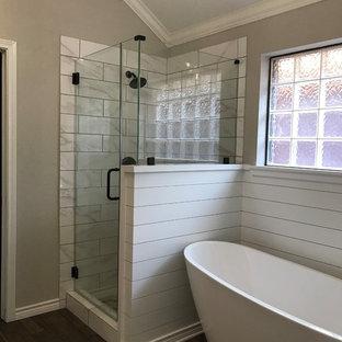 Bild på ett mellanstort lantligt en-suite badrum, med vita skåp, ett fristående badkar, en dusch i en alkov, vit kakel, keramikplattor, grå väggar, klinkergolv i porslin, ett undermonterad handfat, marmorbänkskiva, brunt golv och dusch med gångjärnsdörr