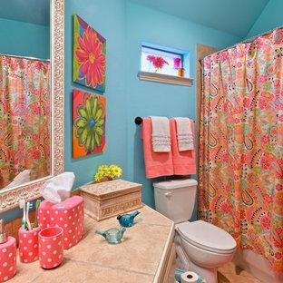 Foto di una stanza da bagno per bambini eclettica di medie dimensioni con lavabo da incasso, ante bianche, top piastrellato, vasca/doccia, piastrelle beige, piastrelle in pietra, pareti blu, pavimento in gres porcellanato, vasca ad alcova e doccia con tenda