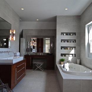 Foto de cuarto de baño principal, urbano, de tamaño medio, con armarios con paneles lisos, puertas de armario de madera en tonos medios, bañera encastrada, baldosas y/o azulejos grises, baldosas y/o azulejos de cemento, paredes grises, suelo de azulejos de cemento, lavabo de seno grande y encimera de madera