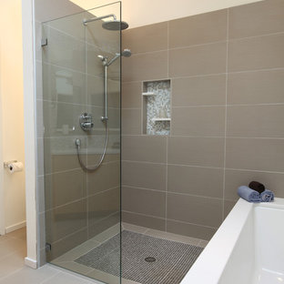This is an example of a large retro bathroom in Seattle with a submerged sink, engineered stone worktops, a submerged bath, grey tiles, porcelain flooring, flat-panel cabinets, light wood cabinets, a one-piece toilet, porcelain tiles and white walls.