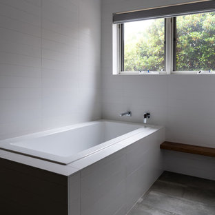 Foto di una stanza da bagno padronale moderna di medie dimensioni con vasca da incasso, doccia aperta, WC monopezzo, piastrelle bianche, piastrelle in ceramica, pareti bianche, pavimento in cementine, lavabo a colonna, top alla veneziana, pavimento grigio e doccia aperta