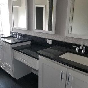 Großes Modernes Badezimmer En Suite mit Falttür-Duschabtrennung, Schrankfronten mit vertiefter Füllung, weißen Schränken, Eckbadewanne, Duschnische, grauer Wandfarbe, Porzellan-Bodenfliesen, Unterbauwaschbecken, Quarzwerkstein-Waschtisch, schwarzem Boden und schwarzer Waschtischplatte in Dallas