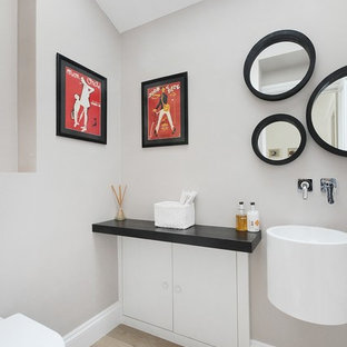 Modelo de cuarto de baño minimalista con lavabo suspendido, armarios con paneles lisos y puertas de armario blancas