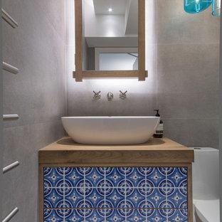 Idee per una piccola stanza da bagno per bambini bohémian con ante in legno scuro, doccia aperta, WC monopezzo, piastrelle blu, pareti grigie e top in legno