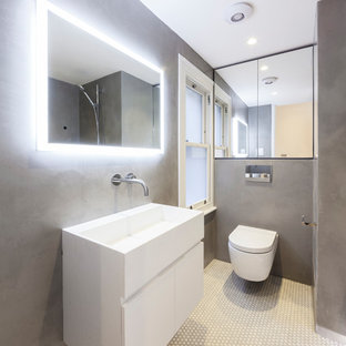 This is an example of a contemporary bathroom in London with flat-panel cabinets, white cabinets, a wall mounted toilet, grey walls, a wall-mounted sink and white floors.