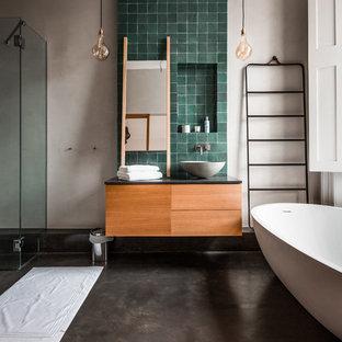 Großes Modernes Duschbad mit freistehender Badewanne, Terrakottafliesen, beiger Wandfarbe, Waschtisch aus Holz, flächenbündigen Schrankfronten, Betonboden, Aufsatzwaschbecken, grauem Boden, Falttür-Duschabtrennung, hellbraunen Holzschränken und grünen Fliesen in London
