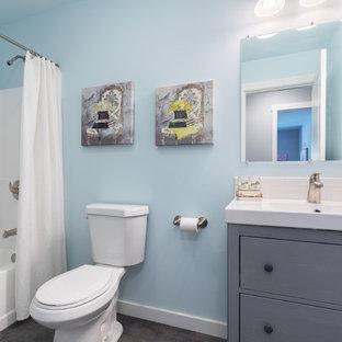 Aménagement d'une salle d'eau classique de taille moyenne avec un placard en trompe-l'oeil, des portes de placard grises, une baignoire en alcôve, un combiné douche/baignoire, un WC séparé, un mur bleu, sol en stratifié, un lavabo intégré, un plan de toilette en quartz modifié, un sol marron, une cabine de douche avec un rideau et un plan de toilette blanc.