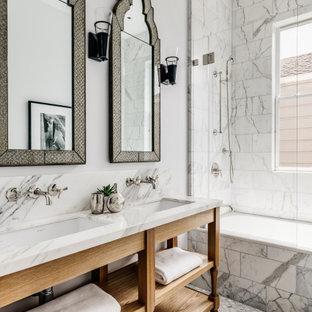 Modelo de cuarto de baño principal, clásico renovado, con armarios abiertos, puertas de armario de madera oscura, bañera encastrada, combinación de ducha y bañera, baldosas y/o azulejos grises, paredes grises, lavabo bajoencimera, suelo gris y encimeras grises