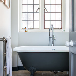 Design ideas for a traditional bathroom in Other with a claw-foot bath, white walls and brown floors.