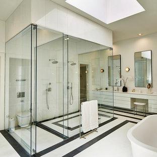 Foto på ett mycket stort funkis en-suite badrum, med släta luckor, vita skåp, ett fristående badkar, en kantlös dusch, en vägghängd toalettstol, svart och vit kakel, glasskiva, vita väggar, marmorgolv, ett integrerad handfat, bänkskiva i kvartsit, vitt golv och dusch med gångjärnsdörr