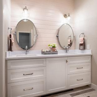 Ejemplo de cuarto de baño principal, de estilo de casa de campo, de tamaño medio, con armarios estilo shaker, puertas de armario blancas, paredes grises, suelo vinílico, lavabo bajoencimera, encimera de cuarzo compacto, suelo beige y encimeras blancas