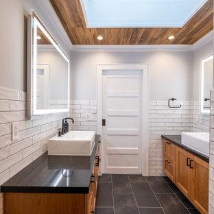 Foto på ett mellanstort funkis svart en-suite badrum, med skåp i shakerstil, skåp i mellenmörkt trä, ett badkar i en alkov, en dusch/badkar-kombination, vit kakel, tunnelbanekakel, klinkergolv i porslin, ett fristående handfat, bänkskiva i akrylsten, grått golv och dusch med skjutdörr