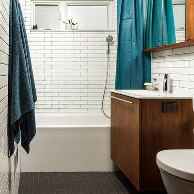Mid-sized eclectic white tile and ceramic tile porcelain tile and black floor bathroom photo in Minneapolis with flat-panel cabinets, brown cabinets, a wall-mount toilet, white walls and an integrated sink