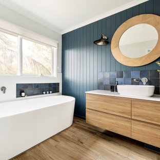 Design ideas for a contemporary master bathroom in Melbourne with flat-panel cabinets, light wood cabinets, a freestanding tub, multi-coloured tile, green walls, a vessel sink, beige floor and white benchtops.