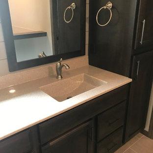Modelo de cuarto de baño principal, tradicional renovado, grande, con armarios estilo shaker, puertas de armario de madera en tonos medios, bañera encastrada, sanitario de dos piezas, paredes grises, lavabo integrado, encimera de ónix y encimeras beige