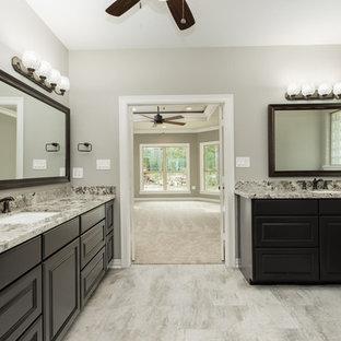 Idéer för mycket stora amerikanska en-suite badrum, med luckor med upphöjd panel, bruna skåp, en öppen dusch, en toalettstol med separat cisternkåpa, beige kakel, spegel istället för kakel, beige väggar, klinkergolv i porslin, ett undermonterad handfat, granitbänkskiva, grått golv och med dusch som är öppen