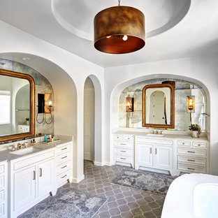 Inspiration for a large mediterranean ensuite bathroom in Dallas with white cabinets, a submerged sink, a submerged bath, white walls, terracotta flooring, engineered stone worktops, grey tiles, cement tiles and recessed-panel cabinets.