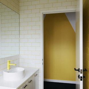 Badezimmer mit weißen Schränken, gelben Fliesen, Keramikfliesen, gelber Wandfarbe und Aufsatzwaschbecken in Melbourne