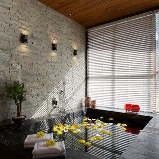Exemple d'une salle de bain principale asiatique avec un bain bouillonnant, un carrelage de pierre et un sol noir.